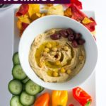A bowl of smooth and creamy hummus surrounded by vegetable chips, mini bell peppers, cucumbers, and kalamata olives.
