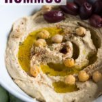 A close-up view of a bowl of smooth and creamy hummus with a handful of kalamata olives, chickpeas, a drizzle of olive oil, and a sprinkle of paprika on top.