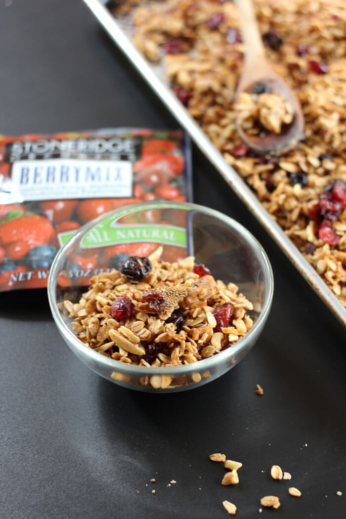 A bowl of tasty everything granola with dried fruit.