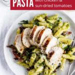 A plate of creamy pesto pasta topped with sun-dried tomatoes and grilled chicken. A perfect meal for any night!