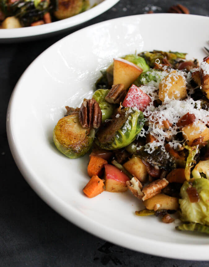 Sweet & Savory Pan Roasted Brussels Sprouts with grated parmesan served on a white dish.