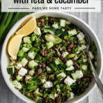 A three bean salad with feta and cucumber served in a large bowl with lemon wedges.