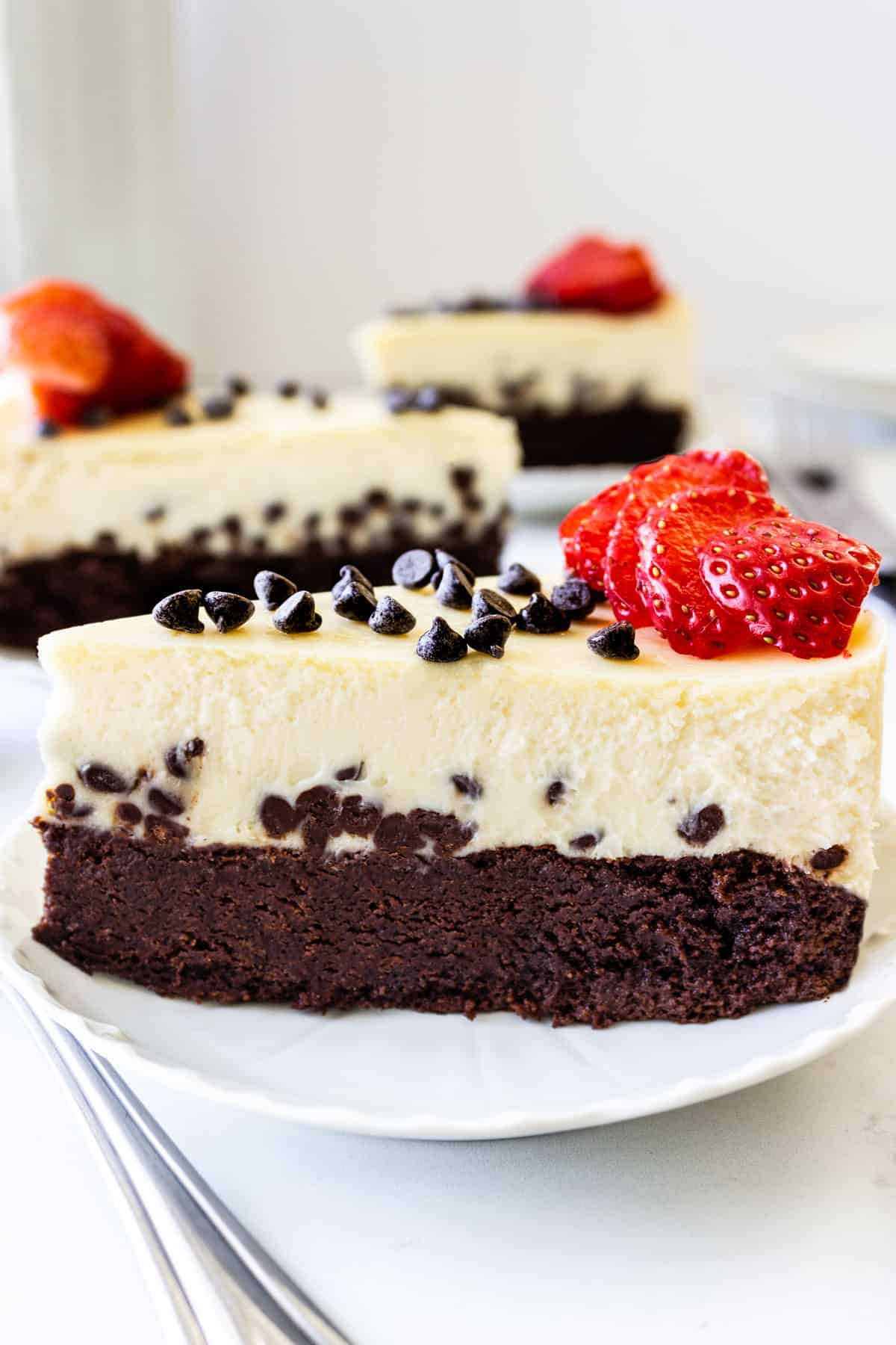 Profile of three slices of chocolate chip brownie cheesecake topped with sliced strawberries and mini chocolate chips.