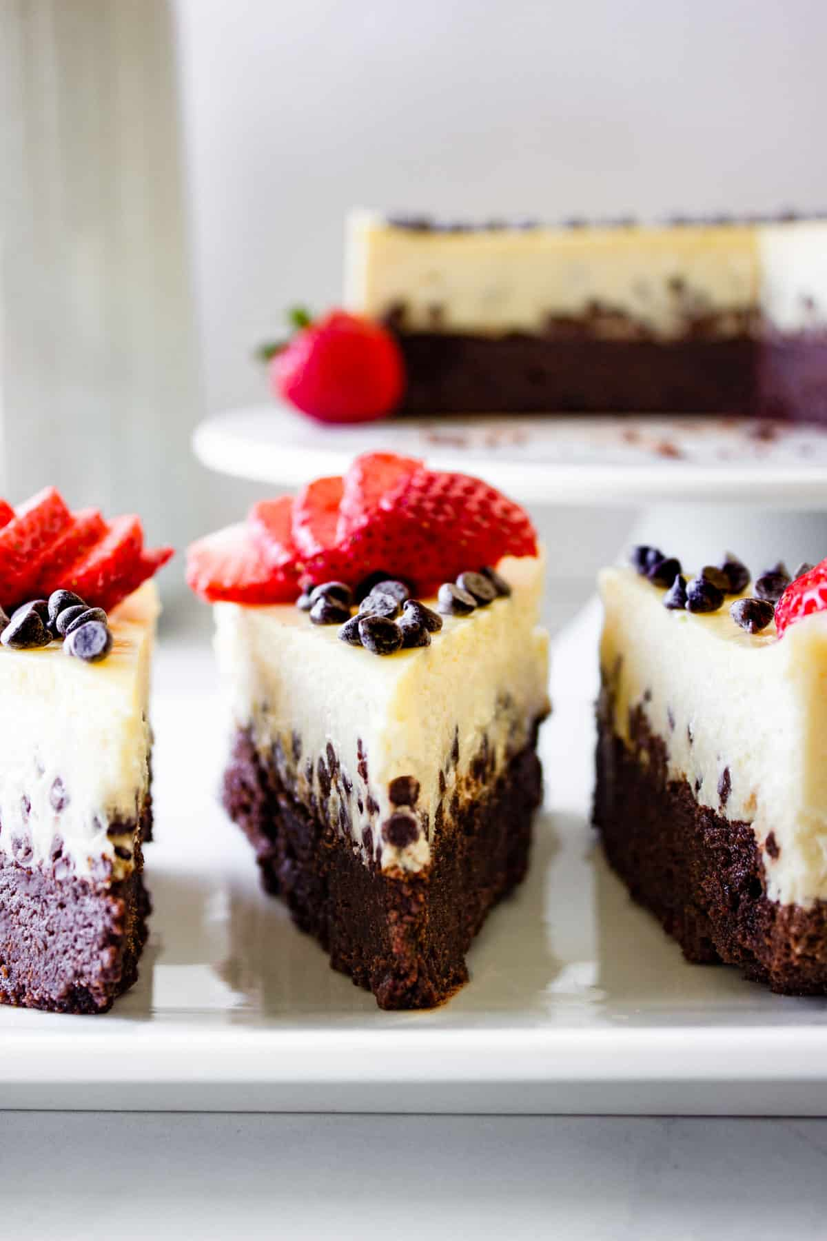 Two distinct layers of brownie and cheesecake in this chocolate chip brownie cheesecake topped with sliced strawberries.