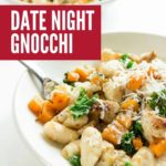 Two white bowls on a white countertop with sliced grilled chicken with gnocchi, sautéed butternut squash, and kale in a creamy sauce topped with grated parmesan.