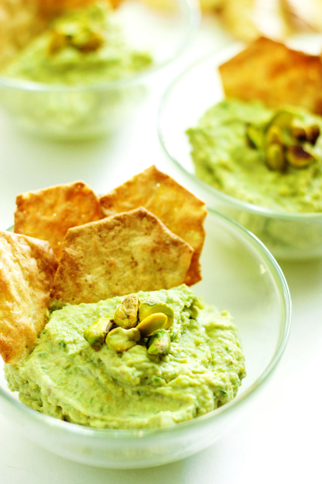 A close-up of several serving bowls of green garlic dips topped with pistachios and served with crackers.