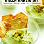 Single serving size bowls with green garlic dip topped with pistachios and served with crackers.