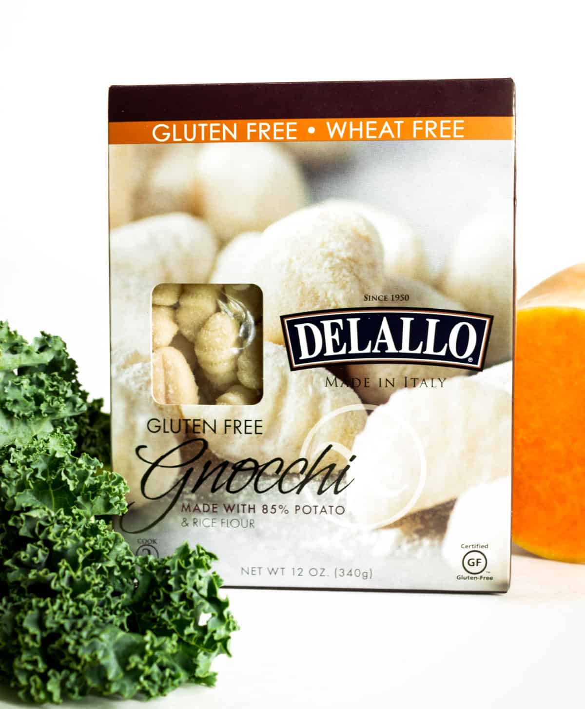 A box of gluten free Delallo brand gnocchi sits next to some green kale and a butternut squash.