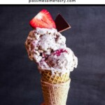 A hand is holding an ice cream cone with two scoops ice cream topped with a strawberry and chocolate.