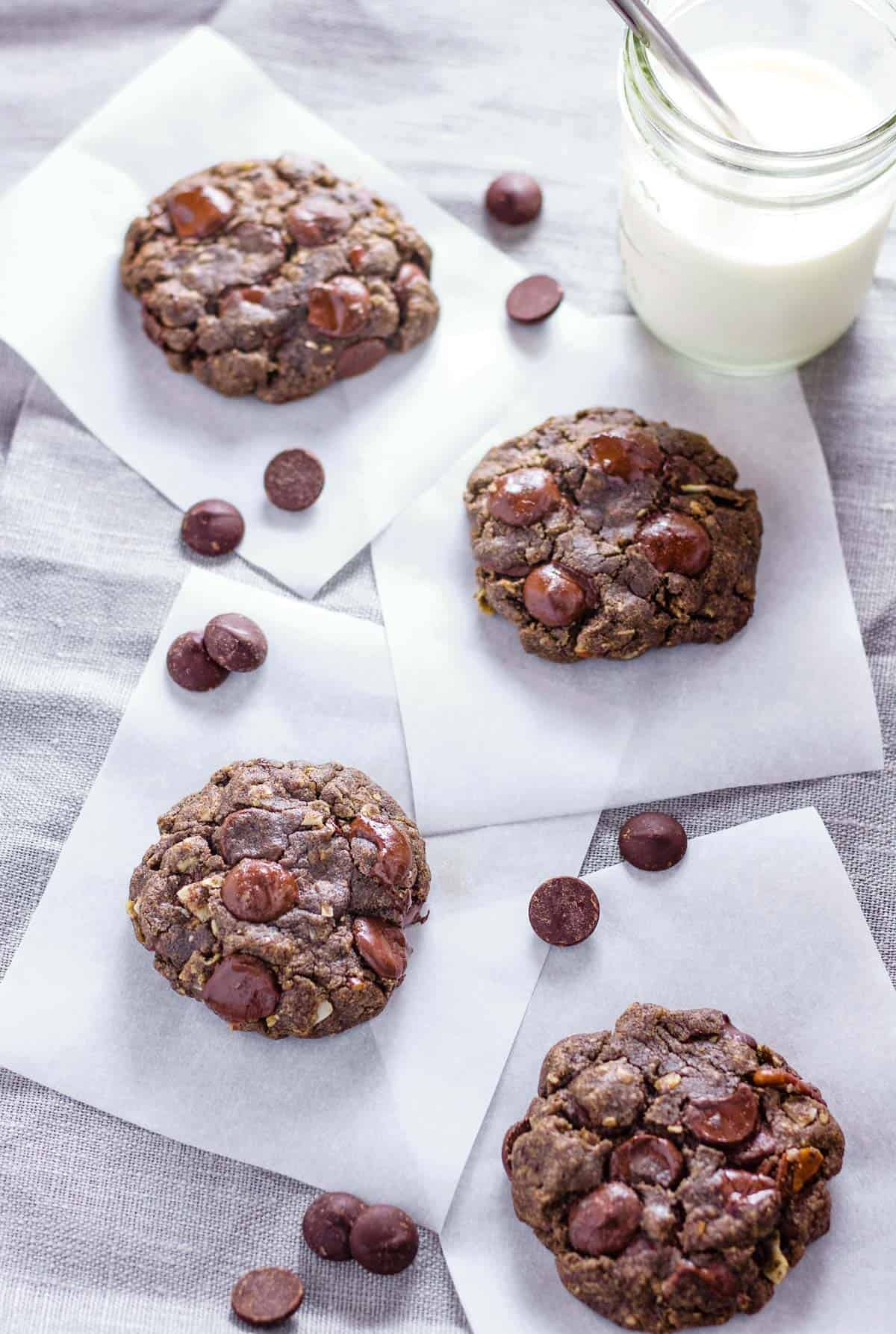 Cookies are set out on a parchment squares with chocolate chips sprinkled about.