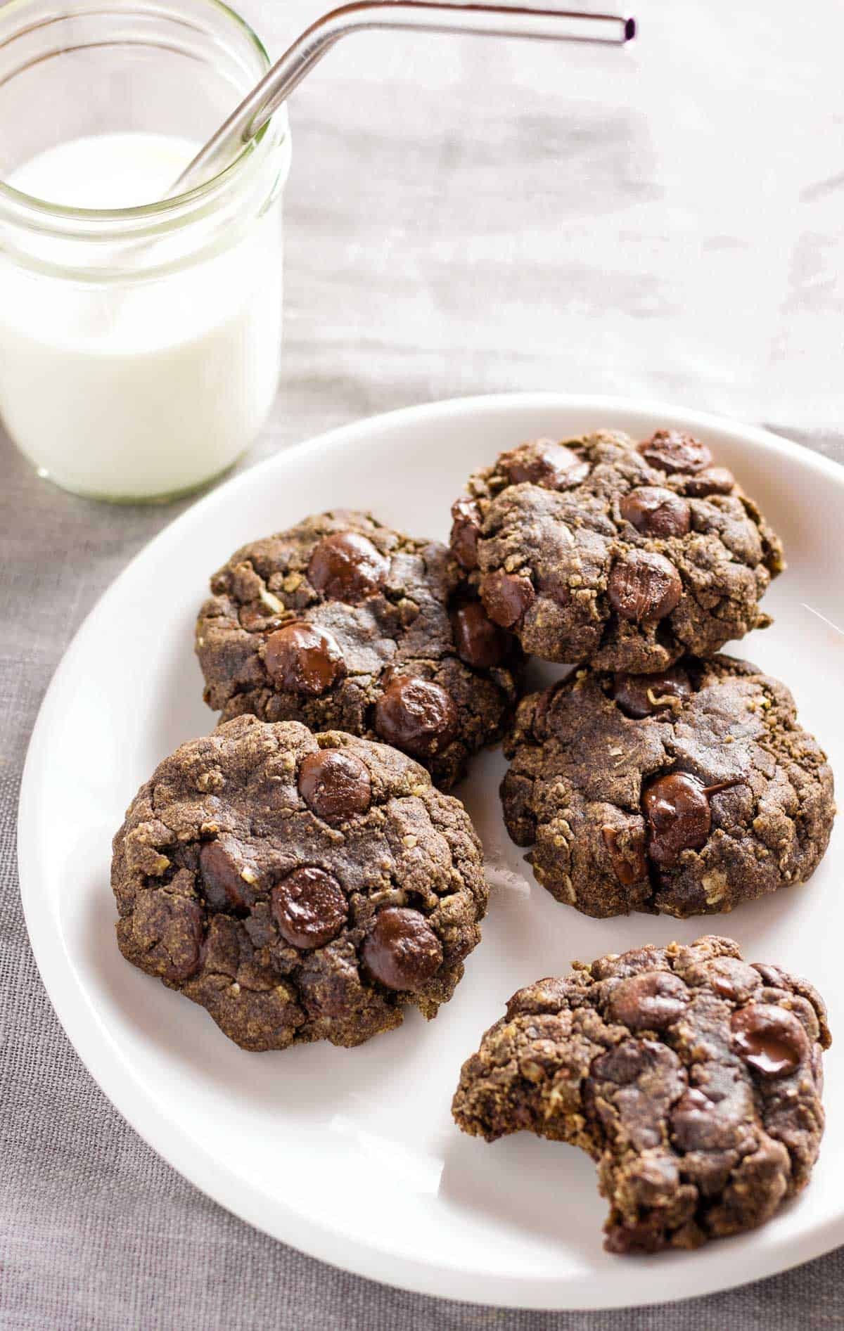 A plate of cookies with a mason jar of milk.
