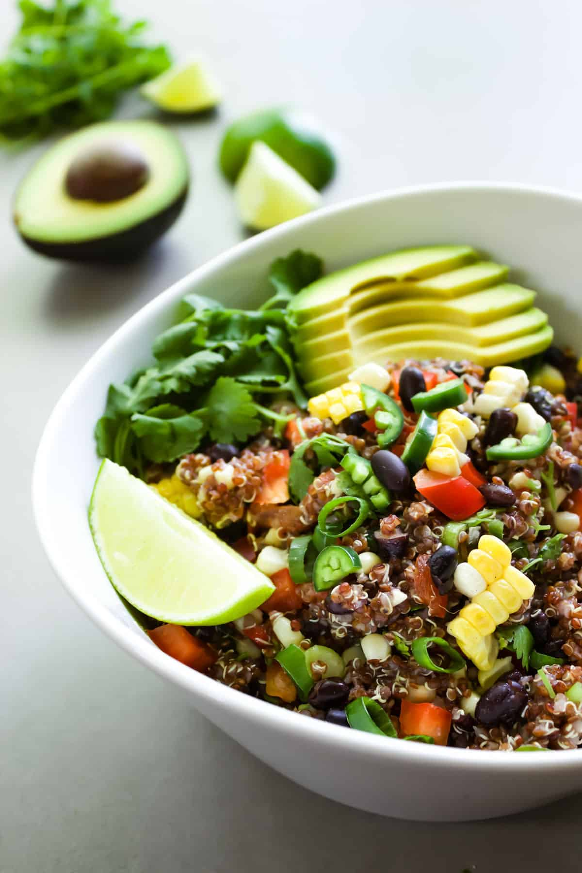 A bowl of spicy red quinoa salad served with lime and avocado.
