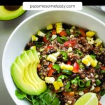 A white bowl with spicy red quinoa salad. A halved avocado, limes, and a fork sit nearby.
