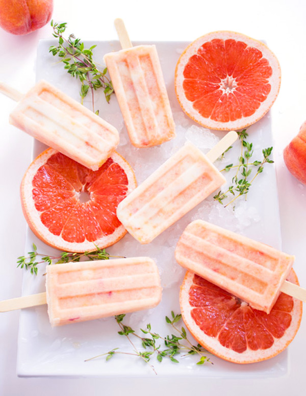 Grapefruit peach popsicles are laid out on a white plate with slices of fresh grapefruit and sprigs of fresh thyme.
