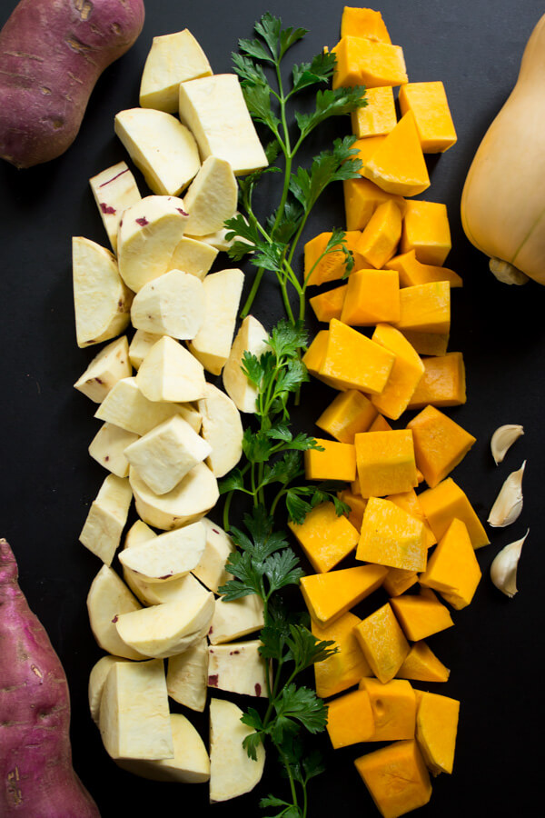 Chopped Japanese sweet potatoes and chopped butternut squash with sprigs of parsley and a few garlic cloves.