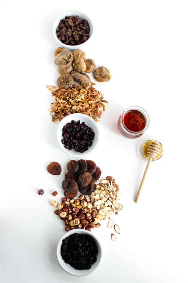 Dried fruit and nuts are laid out on a white background.