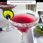 A blueberry margarita with a salted rim and lime wheel.