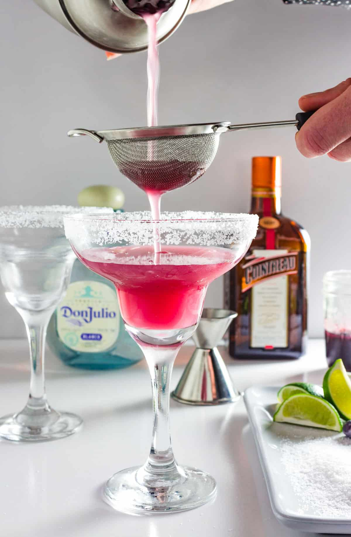 A shaken blueberry margarita is being poured through a strainer into a margarita glass.