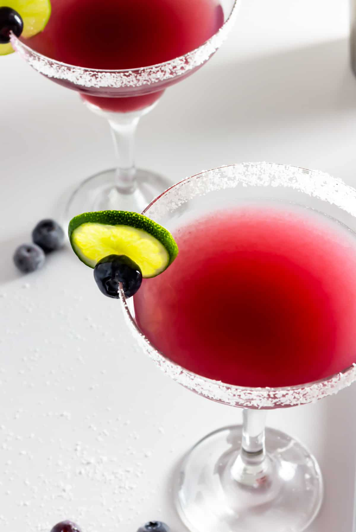 Looking down on two blueberry margaritas garnished with a lime wheel and a blueberry.