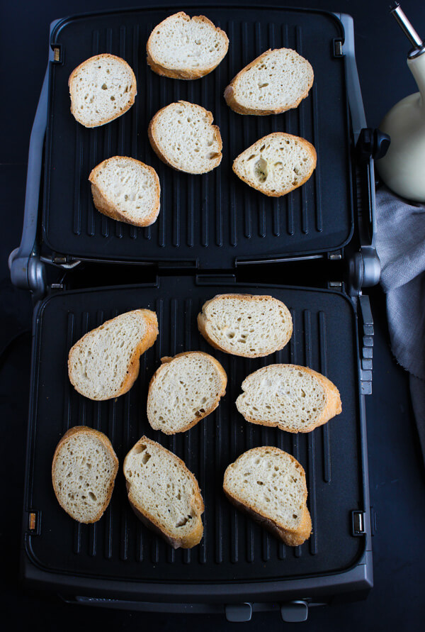 Baguette slices are grilling on a Cuisinart Deluxe Griddler.