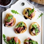 Fig, prosciutto and port salut cheese crostini are topped with a drizzle of balsamic reduction.