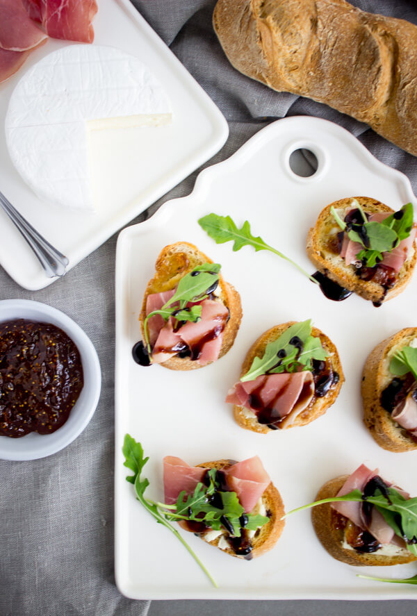 Fig and prosciutto crostini are arranged on a white serving plate as an appetizer. A baguette, brie cheese, slices of prosciutto, and a dish of fig jam sit nearby.