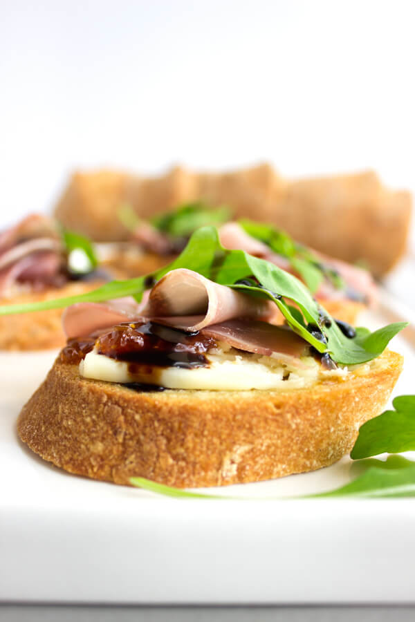 A slice of gluten-free crostini with a schmear of fig jam and port salut cheese topped with a salty slice of prosciutto, peppery arugula, and drizzle of balsamic.