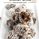 Fruit & nut energy bites are covered in shredded coconut and served on a white rectangular plate.