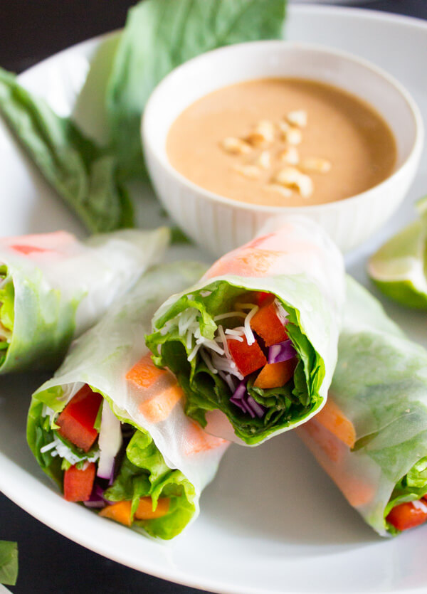 Four vegan salad spring rolls resting on a plate next to each. A small bowl of peanut sauce sits nearby.