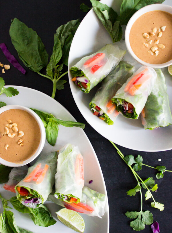 Two plates with vegan salad spring rolls and small dishes of peanut sauce for dipping are ready to be served.