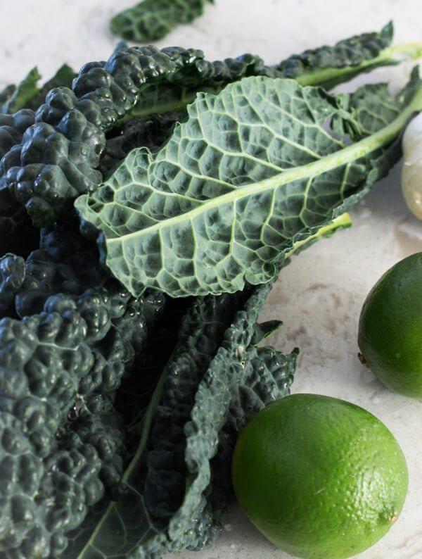 Several large lacinato kale leaves and a couple of limes on a marble countertop.