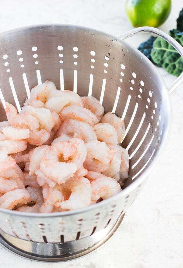A silver colander with fresh medium-sized raw shrimp.