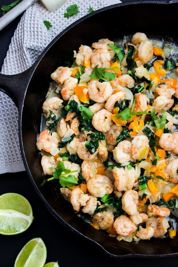A cast iron skillet cooked taco filling consisting of shrimp, orange bell peppers, sautéed kale, garlic and butter. Topped with fresh Italian parsley.