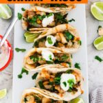 A long plate of shrimp tacos topped with cilantro and sour cream.