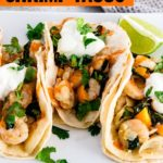 Three shrimp tacos with onions, bell peppers, and sautéed kale. Finished with a big squeeze of lime, a drizzle of hot sauce, fresh cilantro, and a dollop of sour cream all wrapped up in a warm soft corn tortilla with extra lime wedges on the side.