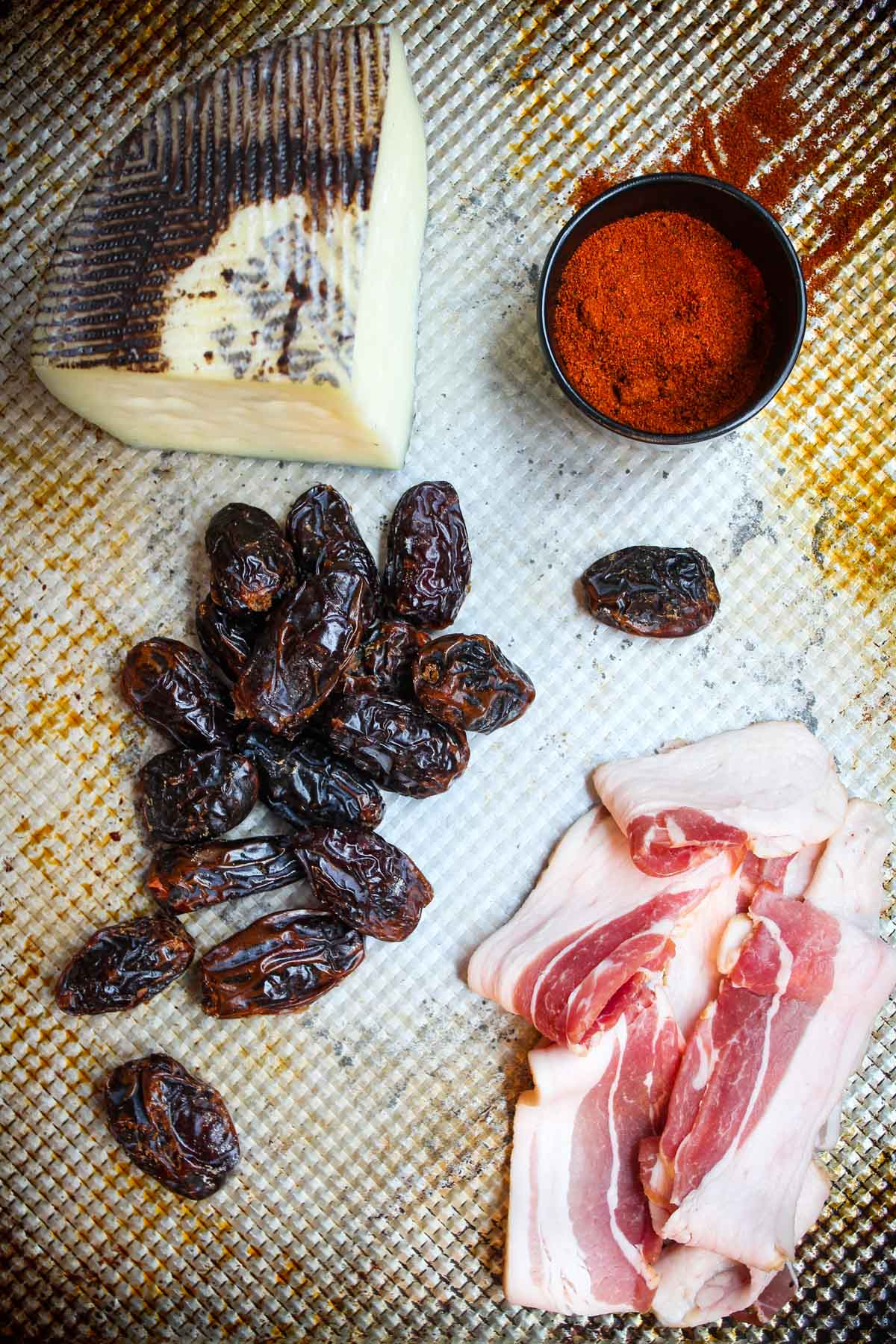 Ingredients for chili bacon wrapped dates are set out. Only four ingredients: Manchego cheese, chili powder, bacon, and dates.