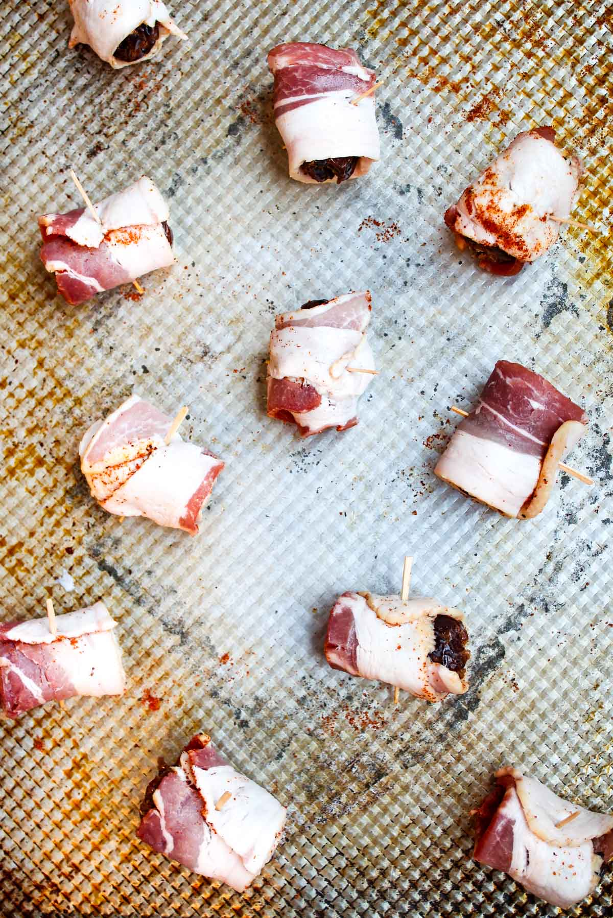 Dates have been wrapped in bacon with chili powder and are spread on a baking sheet ready to be baked.