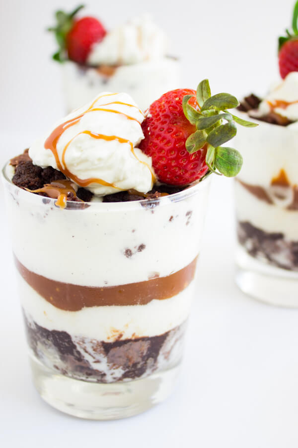 A glass is layered with chocolate fudge brownie vanilla ice cream, salted caramel, more ice cream, and more brownie! Topped with whipped cream, strawberries, and more salted caramel.
