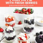 Four chia pudding parfaits served with a bowl of strawberries.