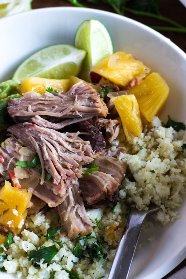 A close-up view of a plate of slow cooker pineapple pulled pork with cauliflower rice and guacamole.