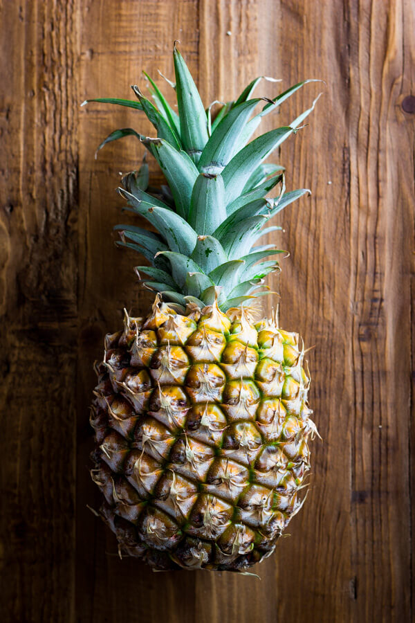A pineapple laying on a rustic wood background.