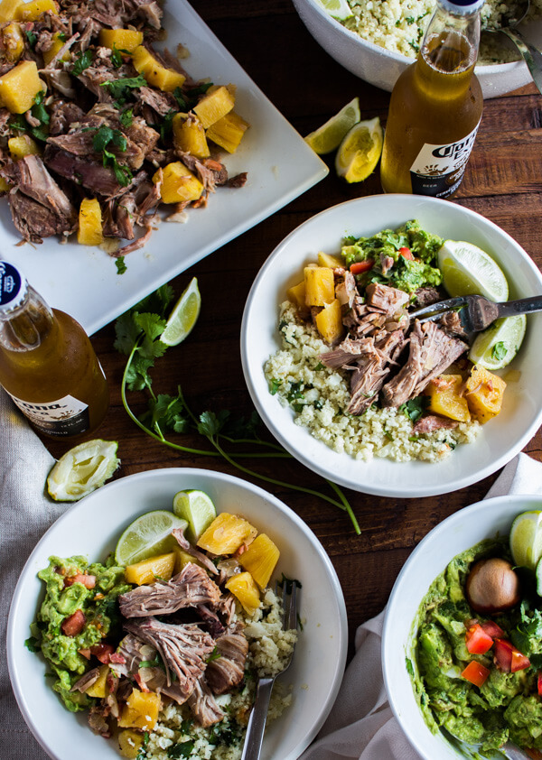 A tabletop with a large serving dish of pineapple pulled pork. A big bowl of guacamole. A bowl of cilantro lime cauliflower rice. And two plates loaded up with food ready to be eaten. Lime wedges and a couple of Corona's nearby.