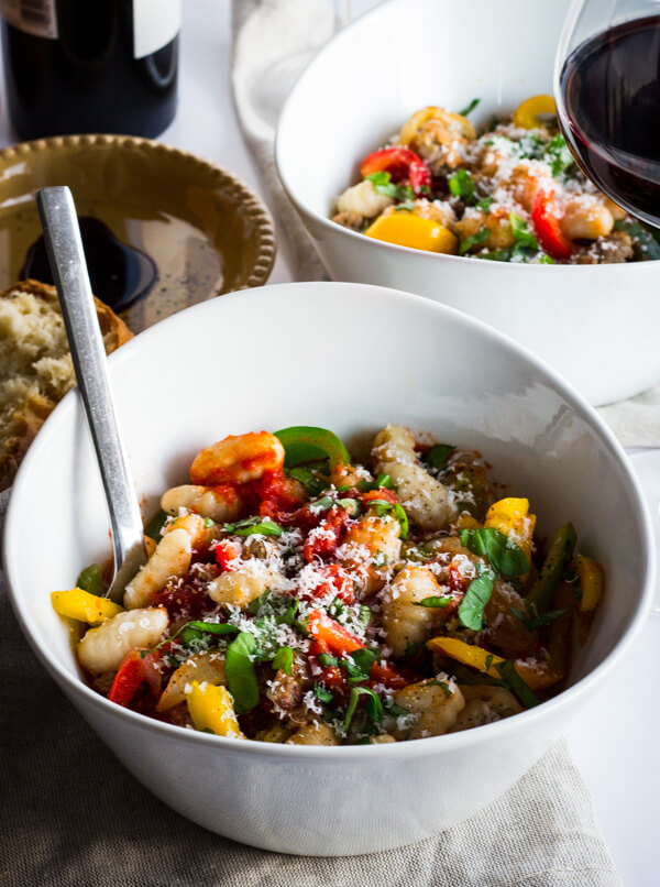 A bowl of gnocchi marinara with Italian sausage and tri-colored bell peppers.