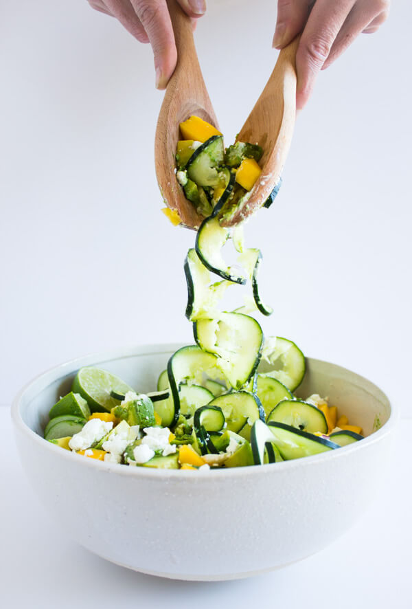 Two hands are reaching into a spiralized cucumber summer salad with serving spoons.