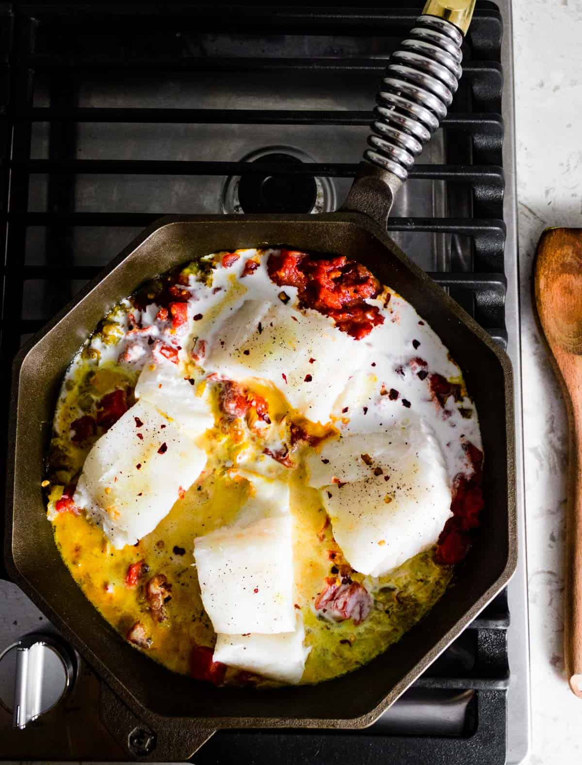 A cast iron skillet on a stovetop cooking coconut tomato curry with cod.