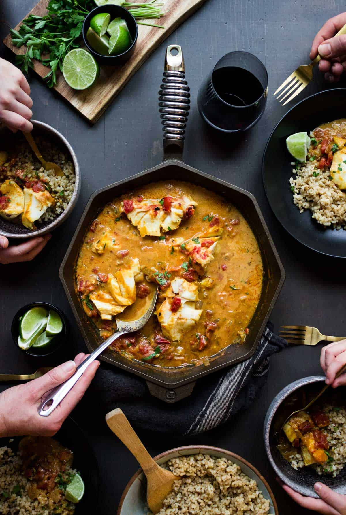 A family gathering around a table with 4 bowls and cast iron skillet of coconut tomato curry with cod and brown rice.