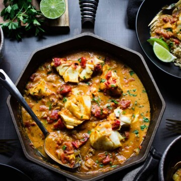 A cast iron skillet and bowls of coconut tomato curry with cod and brown rice. Garnished with lime wedges and Italian parsley.