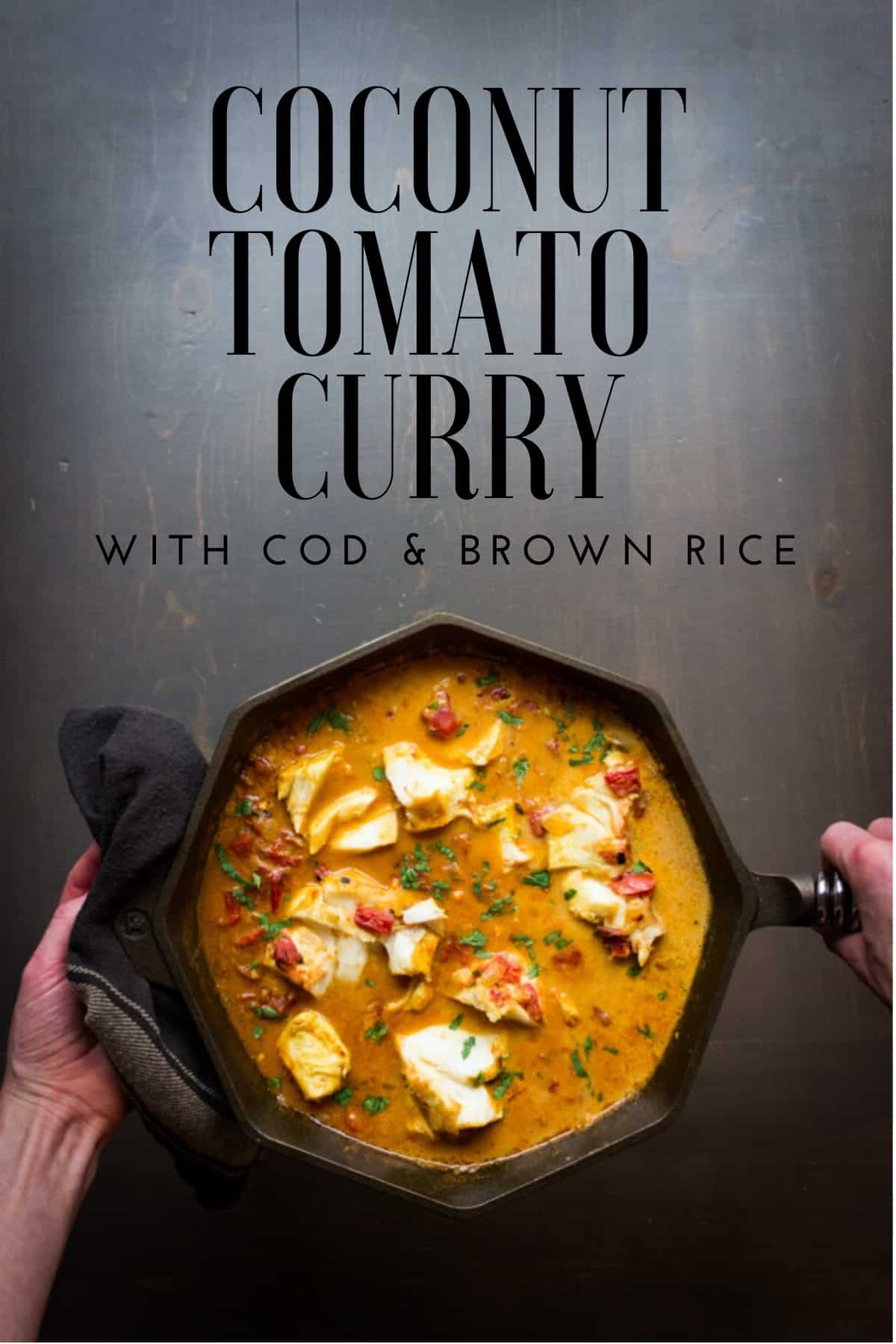 Two hands holding a cast iron skillet with coconut tomato curry and cod.