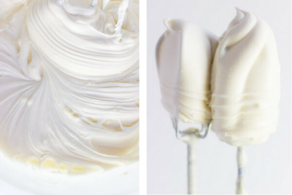A close up view of cream cheese frosting and two mixing beaters covered with smooth and creamy cream cheese frosting.