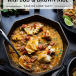 An octagonal cast iron skillet with coconut tomato curry with cod. a bowl of brown rice sits nearby.